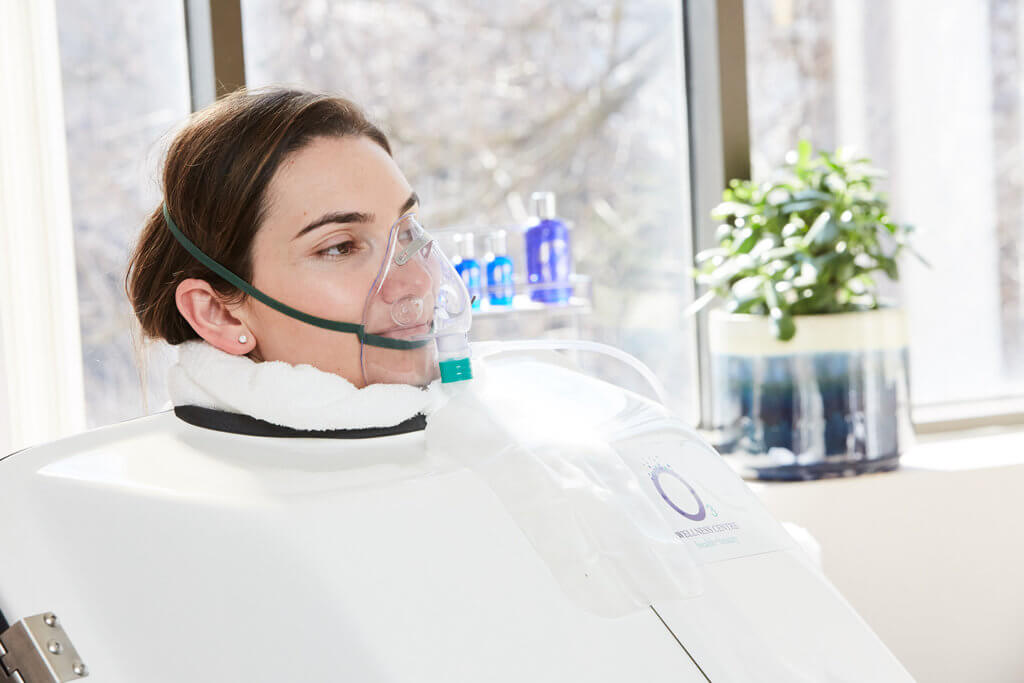 O3 Ozone Sauna - Homepage | Woman sitting in an encapsulated o3 ozone sauna pod with a mask
