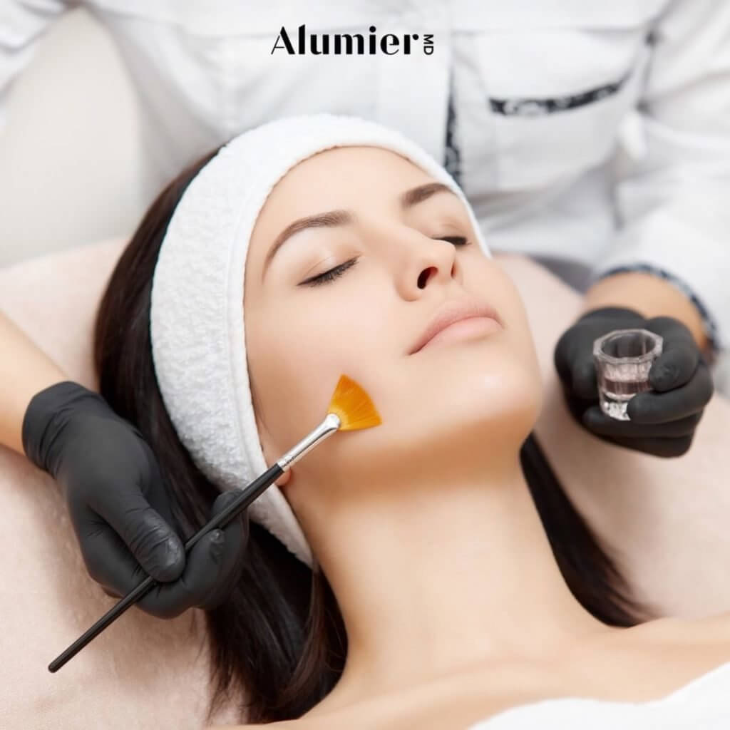Picture of a woman laying face up receiving an paint brush stroke of AlumnierMD branded Chemical Peel